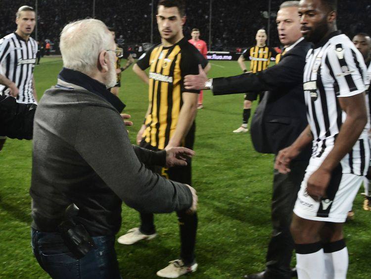 Paok president Ivan Savvidis, centre, took to the pitch after the referee refused a last minute goal