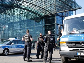 Police officers stand in front of the central train station while a World War Two bomb is defused in Berlin, Germany