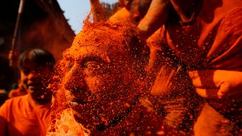 """A devotee gets his face smeared with vermillion powder during """"Sindoor Jatra"""" vermillion powder festival at Thimi, in Bhaktapur, Nepal"""