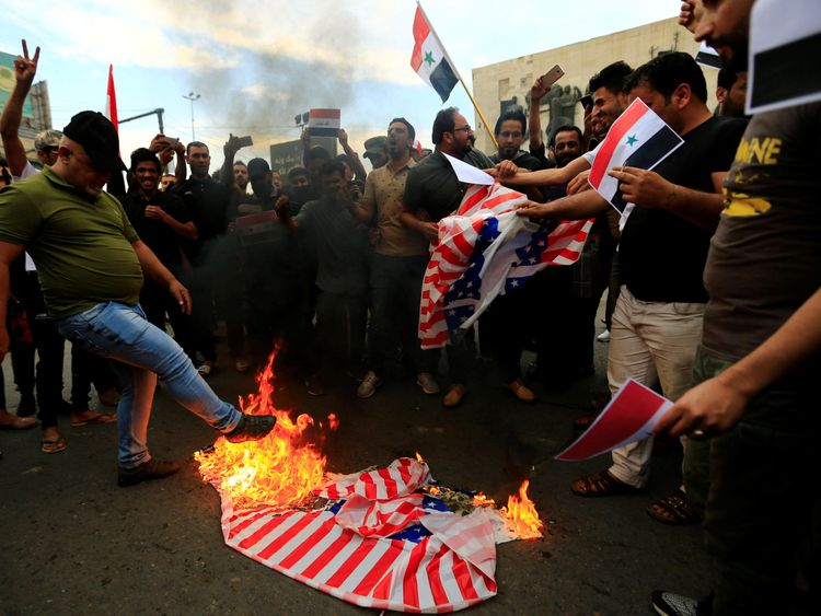 Protesters burn a US flag in Tahrir Square, Baghdad, Iraq