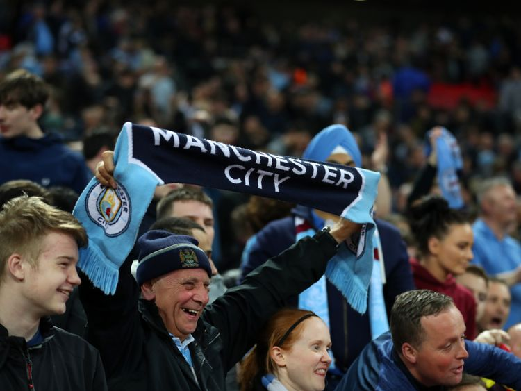 A fan of Manchester City holds up a scarf during the Premier League match between Tottenham Hotspur and Manchester City at Wembley Stadium on April 14, 2018 in London, England