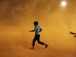 A boy runs for cover during a dust storm in New Delhi, India