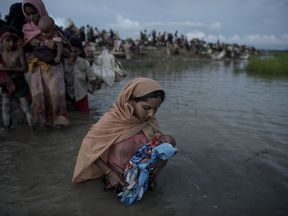 - Rohingya refugees wade while holding a child after crossing the Naf river from Myanmar into Bangladesh in Whaikhyang on October 9, 2017. A top UN official said on October 7 Bangladesh's plan to build the world's biggest refugee camp for 800,000-plus Rohingya Muslims was dangerous because overcrowding could heighten the risks of deadly diseases spreading quickly. The arrival of more than half a million Rohingya refugees who have fled an army crackdown in Myanmar's troubled Rakhine state since A
