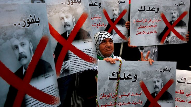 Palestinian demonstrators carry placards of British Prime Minister Balfour while protesting the Balfour Declaration