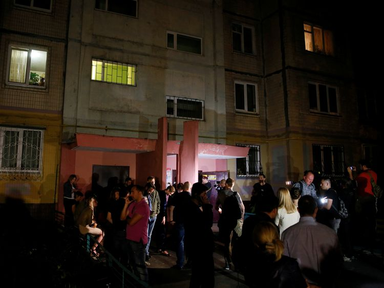 People gather outside the apartment building where Arkady Babchenko was shot