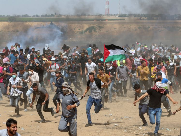 Palestinian demonstrators run for cover from tear gas fired by Israeli forces