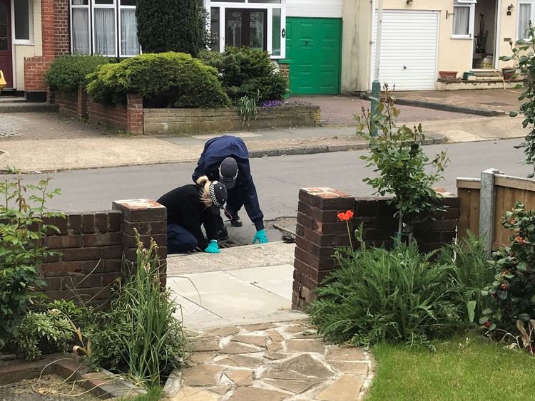 Police officers searching drains in Ashmour Gardens, Romford