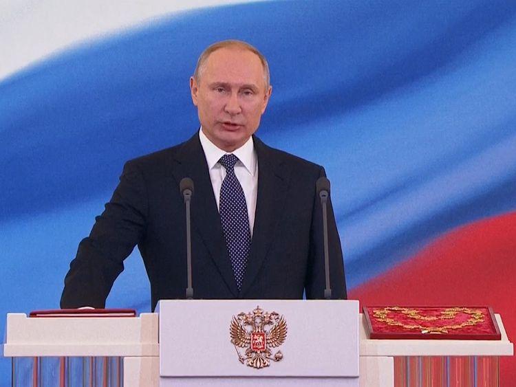 Vladimir Putin is sworn in at the lectern