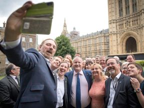 Chris Law takes a picture as the SNP MPs gather outside parliament
