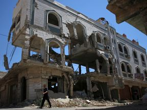 A man walks past a damaged building in the rebel-held city of Inkhil, west of Deraa, Syria, September 7, 2017