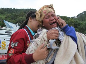 A woman cries as she finds out her family are listed as missing at the Lake Toba ferry port