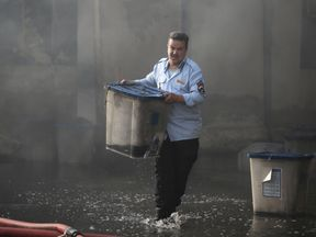 An official carries a ballot box after a fire at a storage site in Baghdad