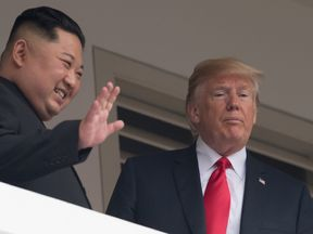 Kim Jong Un and Donald Trump look on from a veranda at their summit