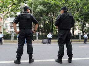 Police officers stand guard at the scene after a man armed with a knife attacked students