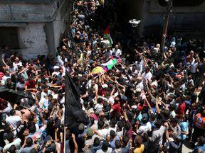 Mourners carry the body of Palestinian nurse Razan Al-Najar