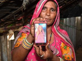 Mohinidevi Nath shows a photo on her phone of her cousin Shantadevi Nath
