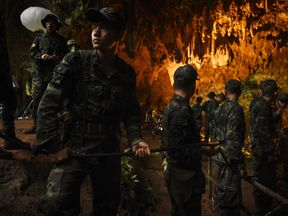 Thai soldiers relay electric cable deep into the Tham Luang cave