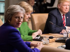 British Prime Minister Theresa May, German Chancellor Angela Merkel and US President Donald Trump participate in a working session of the G7 Summit with in Charlevoix, Quebec, Canada