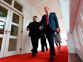 Kim Jong Un and Donald Trump walk together as their one-on-one meeting begins