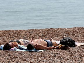 A couple relax in the heat on the beach in Hastings, Sussex