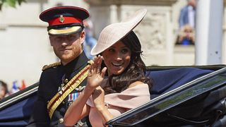 Meghan waves as she and Harry ride to Trooping the Colour