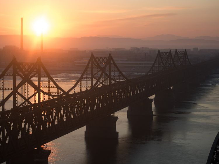 The sun rises over the bridge on the banks of the Yalu River in the Chinese border town of Dandong opposite to the North Korean town of Sinuiju on February 10, 2016