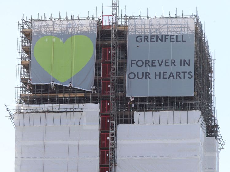 The banners being unfurled at the top of Grenfell Tower