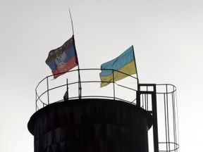 Flags of Ukraine (R) and of the self-proclaimed People's Republic of Donetsk fly on a water tower in the city of Krasny Partizan near Donetsk on December 13, 2014. Russia responded angrily on December 13 to news that US senators had passed a bill calling for fresh sanctions against Moscow and the supply of lethal military aid to Ukraine. AFP PHOTO / VASILY MAXIMOV (Photo credit should read VASILY MAXIMOV/AFP/Getty Images)