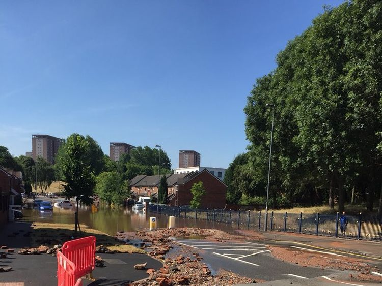 Water has begun to subside, revealing the damage to the road. Pic: West Midlands Fire