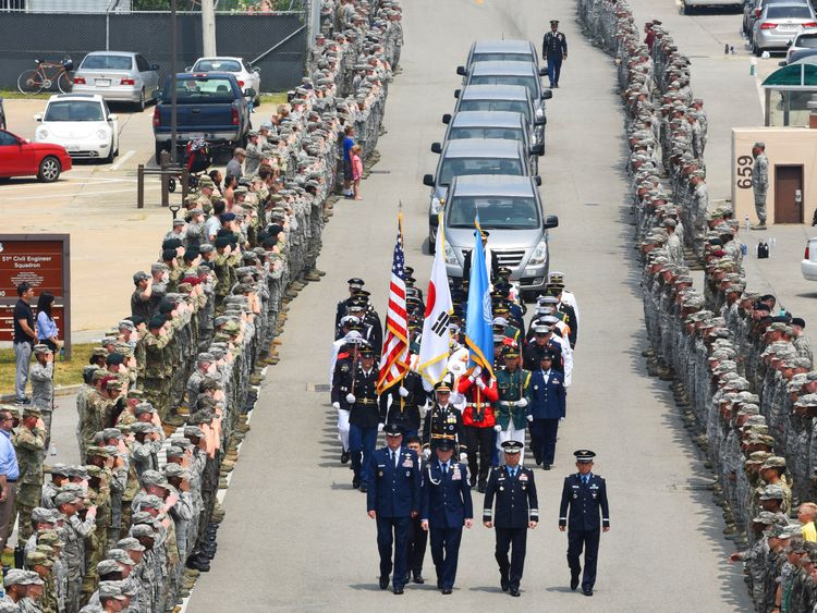 Members of the United Nations Command stand at attention upon the arrival of 55 boxes of soldier remains
