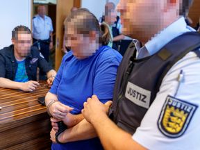 FREIBURG, GERMANY - AUGUST 07: ATTENTION EDITORS: Pixelation done in accordance with court orders. Defendants Christian L. (L) and Berrin T. (C) arrive for their pronouncement of judgement on charges related to sexual abuse of a minor at the regional court in Freiburg, Germany, 07 August 2018. Christian L. and Berrin T. are accused of having offered Berrin's nine-year-old son in Staufen to paedophiles across Europe for sex in an abuse case that has shocked Germany. The couple ran their operation