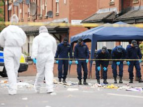 Police from the Tactical Aid Unit carry out a fingertip search