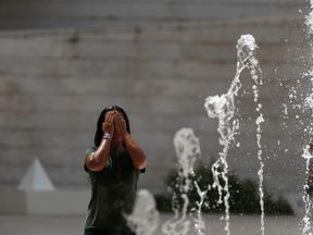 A woman refreshes in a public fountain in Lisbon, Portugal August 4, 2018. REUTERS/Rafael Marchante