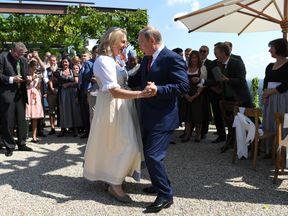 Russian President Vladimir Putin dances with Austrian Foreign Minister Karin Kneissl at her wedding