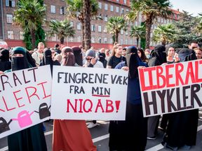 Women wearing niqab to veil their faces take part in a demonstration on August 1, 2018, the first day of the implementation of the Danish face veil ban, in Copenhagen, Denmark. - Denmark's controversial ban on the Islamic full-face veil in public spaces came into force as women protested the new measure which fines anyone wearing the garment. Human rights campaigners have slammed the ban as a violation of women's rights, while supporters argue it enables better integration of Muslim immigrants i