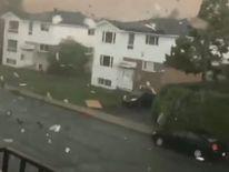 Tornado sweeps through Quebec as debris fly over sky.