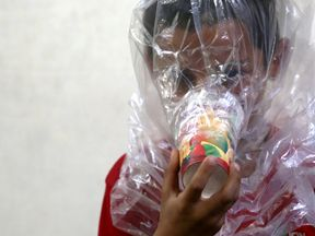 A boy tries on an improvised gas mask in Idlib