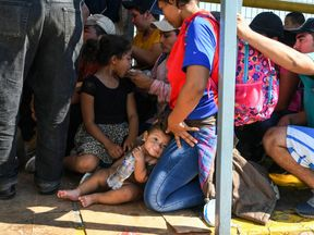 Honduran migrants wait to cross the border from Ciudad Tecun Uman, Guatemala, to Ciudad Hidalgo, Mexico