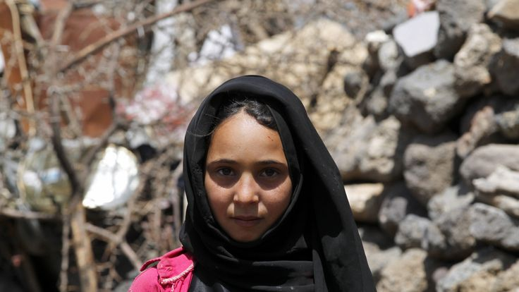 Fatemah Naser ,11 stands outside her family's makeshift shelter at the Dharawan settlement