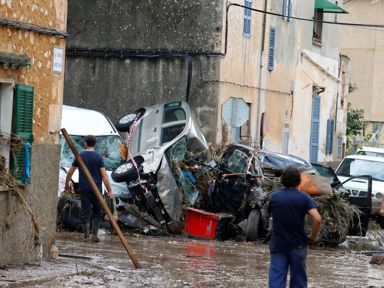 People clear debris as heavy rain and flash floods hit Sant Llorenc de Cardassar on the island of Mallorca