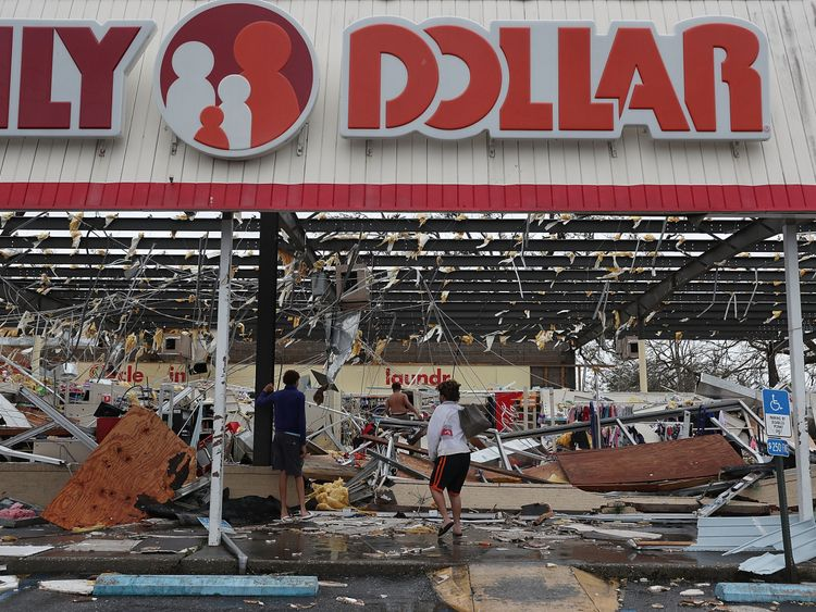 People look on at a damaged store after Hurricane Michael passed through on October 10, 2018 in Panama City, Florida