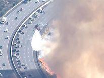 Fire crews attempt to extinguish blaze alongside southern California freeway