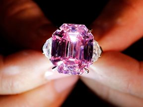 FILE PHOTO: A Christie's staff holds a 18.96 carat Fancy Vivid Pink Diamond during a preview in Geneva, November 8, 2018. REUTERS/Denis Balibouse/File Photo