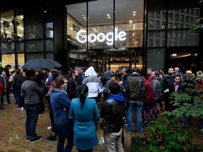 Workers stand outside the Google offices after walking out as part of a global protest over workplace issues, in London