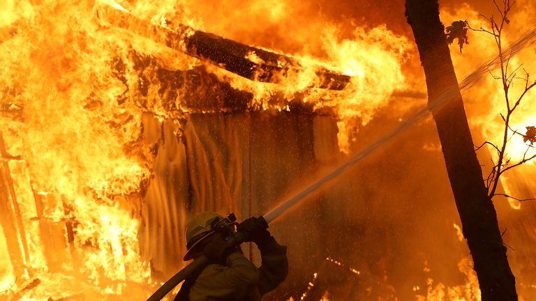 A firefighter battles a wild fire blaze in Magalia, California