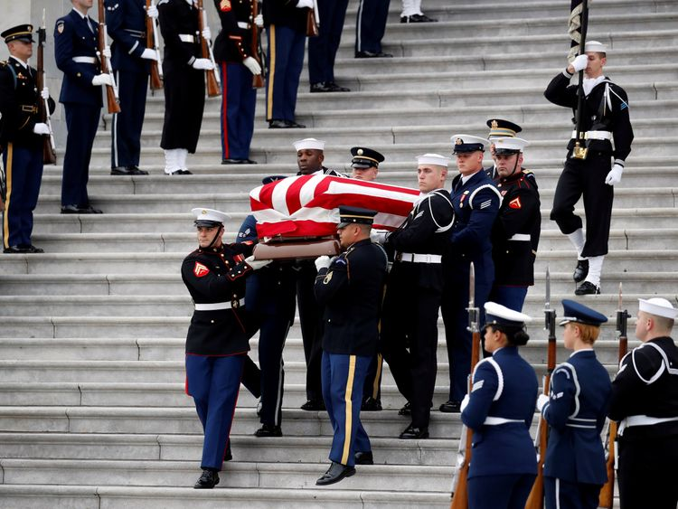 The flag-draped casket of former President George H.W. Bush is carried by a joint services military honour guard from the U.S. Capitol