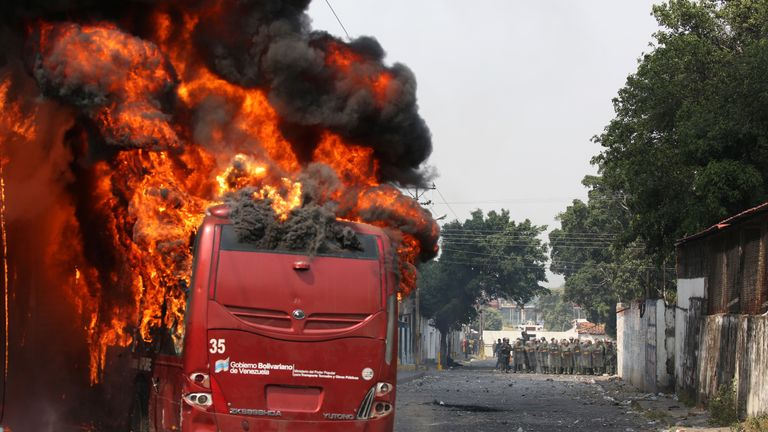 A bus was set on fire by demonstrators as security forces battled for control in Urena